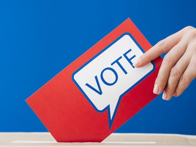 Frau, die ihren stimmzettel in den wahlkasten legt