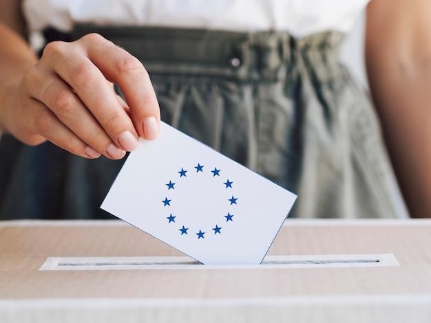 Frau, die ihren stimmzettel in einen kasten einsetzt