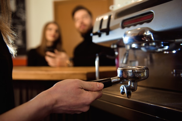 Frau, die ihren tag auf einem neuen job als barista beginnt. arbeiten in einem café.
