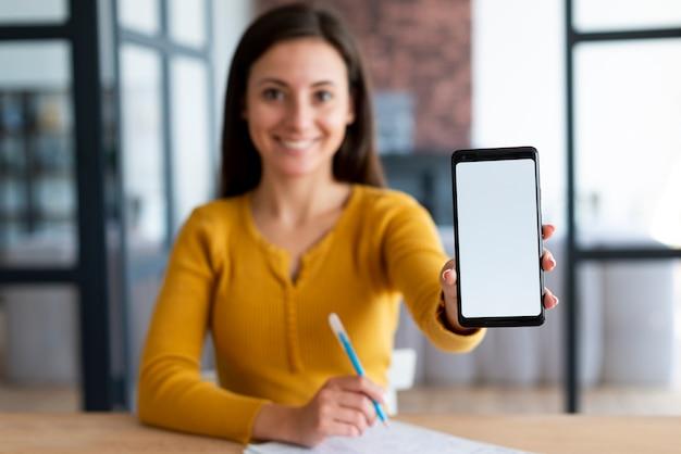 Frau, die ihren telefonbildschirm zeigt