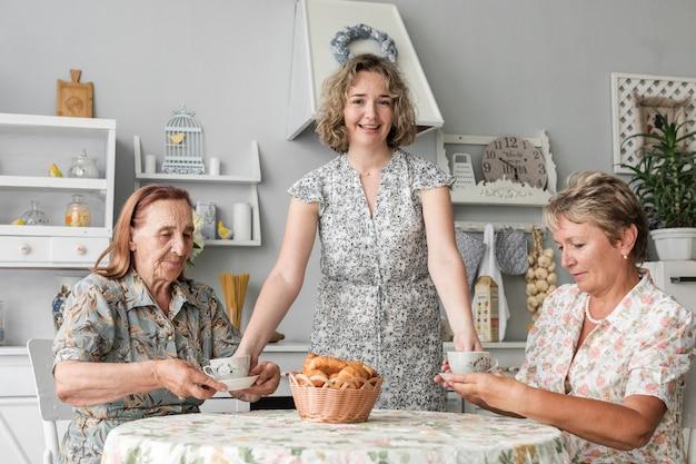 Frau, die ihrer mutter und oma in der küche kaffeetasse gibt