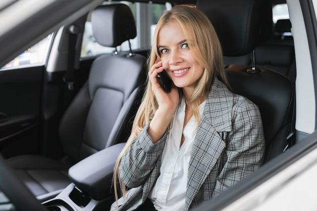 Frau, die im auto bei der unterhaltung am telefon sitzt