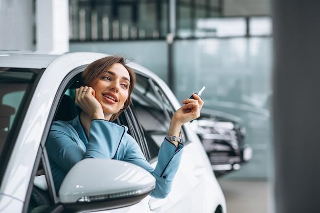 Frau, die im auto hält schlüssel sitzt