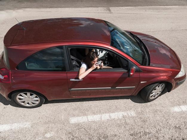 Frau, die im auto macht foto mit kamera auf der straße sitzt