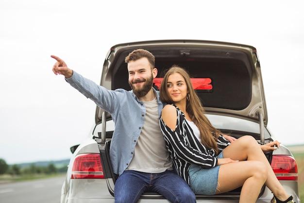 Frau, die im autokofferraum betrachtet seinen freund irgendwo zeigt sitzt