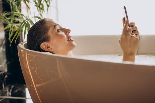 Frau, die im bad mit blasen entspannt und am telefon spricht