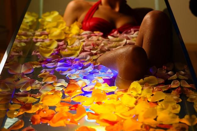 Frau, die im badekurort mit farbtherapie badet