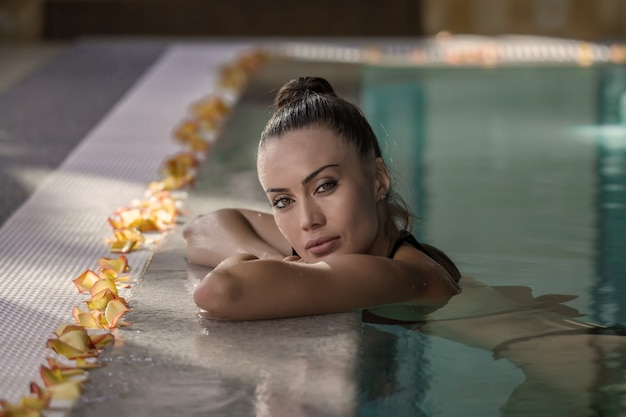 Frau, die im badekurortpool sich entspannt