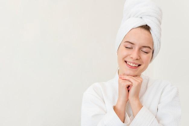 Frau, die im bademantel aufwirft und mit kopienraum lächelt