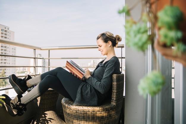 Frau, die im balkon betrachtet fotoalbum sitzt