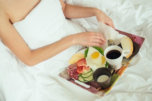 Frau, die im bett frühstückt. fensterlicht