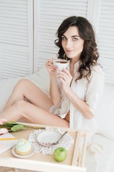 Frau, die im bett frühstückt