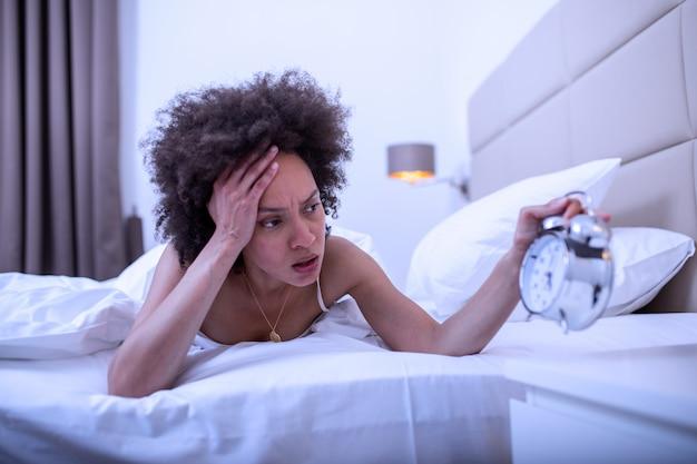 Frau, die im bett liegt und an schlaflosigkeit leidet, schlaflose und verzweifelte frau, die nachts wach ist und nicht schlafen kann, sich frustriert und besorgt fühlt und an schlaflosigkeit bei schlafstörung leidet