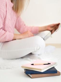Frau, die im bett sitzt und digitales tablett verwendet