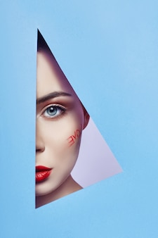 Frau, die im blauen dreieckloch schaut