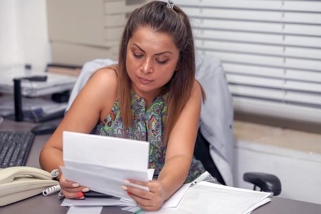 Frau, die im büro mit vielen dokumenten arbeitet. viel papierkram im büro.