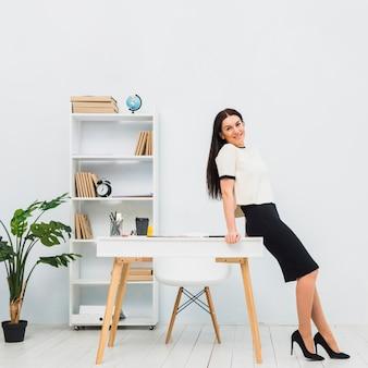Frau, die im büro sich lehnt auf tabelle steht