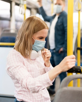 Frau, die im bus mit gesichtsmaske hustet
