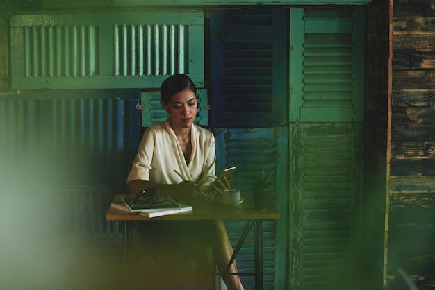 Frau, die im café sitzt, smartphone betrachtet und in notizbuch schreibt