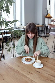 Frau, die im café sitzt und kuchen isst