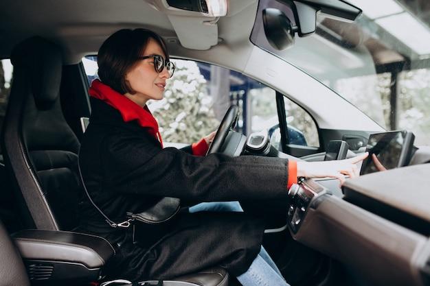 Frau, die im elektroauto sitzt, während es auflädt