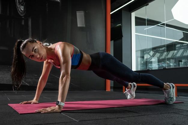 Frau, die im fitnessstudio mit geraden armen frontplank durchführt