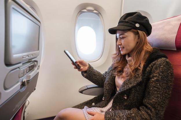 Frau, die im flug smartphone in der flugzeugzeit verwendet.