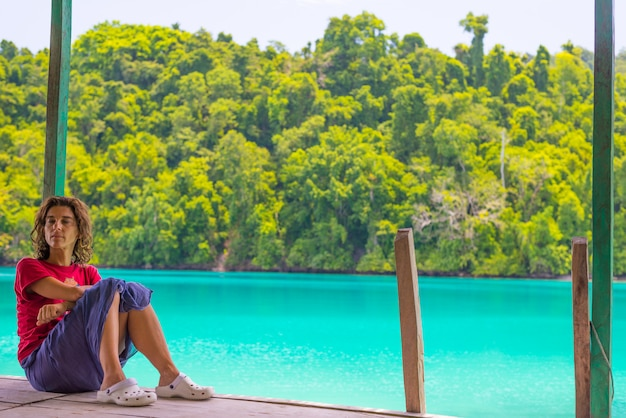 Frau, die im fremdenverkehrsort auf buntem meer der fern-togean-inseln, sulawesi, indonesien sich entspannt.