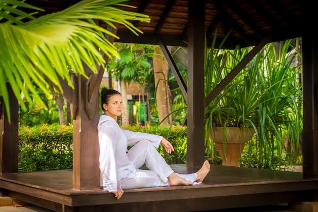 Frau, die im gazebo sitzt, nachdem yoga geübt worden ist