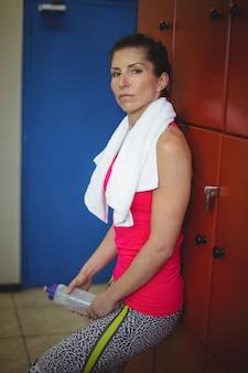 Frau, die im gymnastikumkleideraum nach dem training steht
