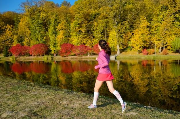 Frau, die im herbstpark läuft, schöner mädchenläufer, der draußen joggt, training für marathon, training und fitnesskonzept