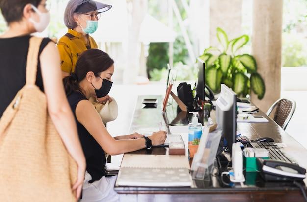 Frau, die im hotel medizinische maske gegen virus trägt prüft.