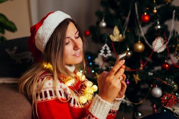 Frau, die im internet für weihnachten unter verwendung des smartphone hängt. mädchen, das alleine neues jahr zu hause feiert. soziales netzwerk