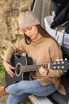 Frau, die im kofferraum des autos während eines straßenausfluges sitzt und gitarre spielt