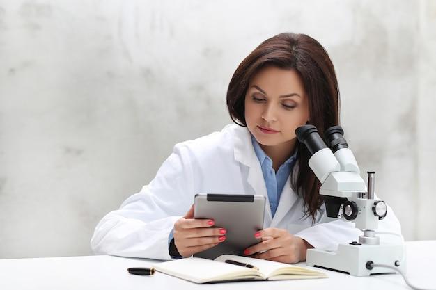 Frau, die im labor mit einem mikroskop arbeitet Kostenlose Fotos