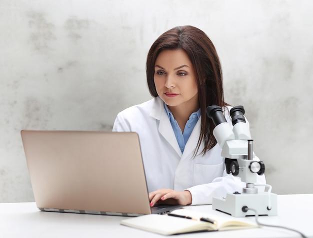 Frau, die im labor mit einem mikroskop arbeitet