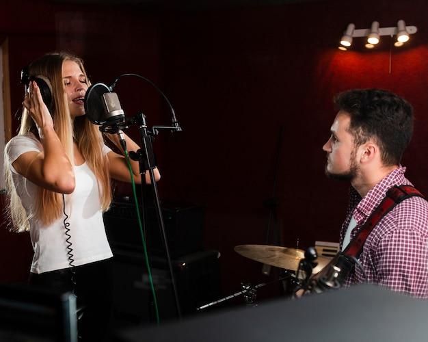 Frau, die im mikrofon und im kerl spielt gitarre singt