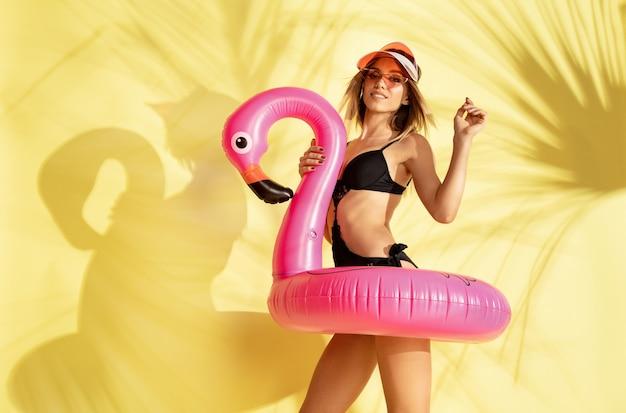 Frau, die im modischen bodysuit und im rosa flamingo aufwirft
