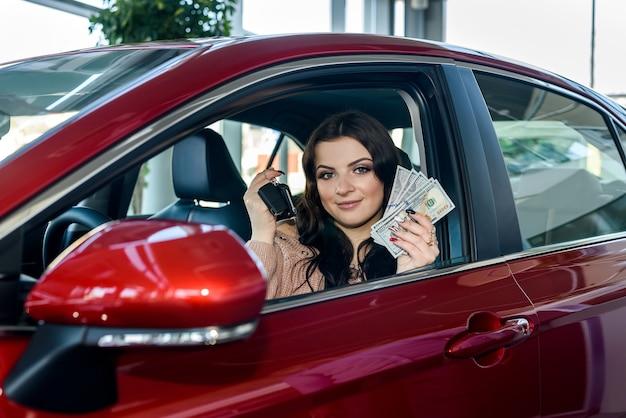 Frau, die im neuen auto sitzt und dollar und schlüssel zeigt