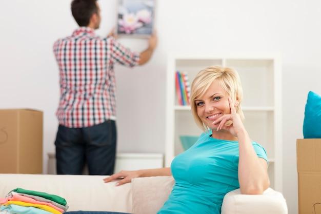 Frau, die im neuen haus und im mann sitzt, der wohnzimmer verziert