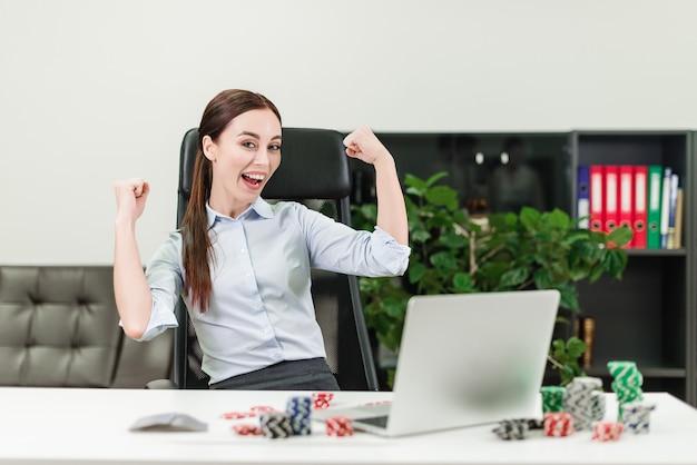Frau, die im on-line-kasino und im poker über laptop im büro spielt und gewinnt