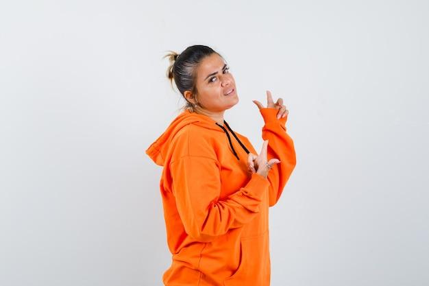 Frau, die im orangefarbenen hoodie nach oben zeigt und selbstbewusst aussieht. .