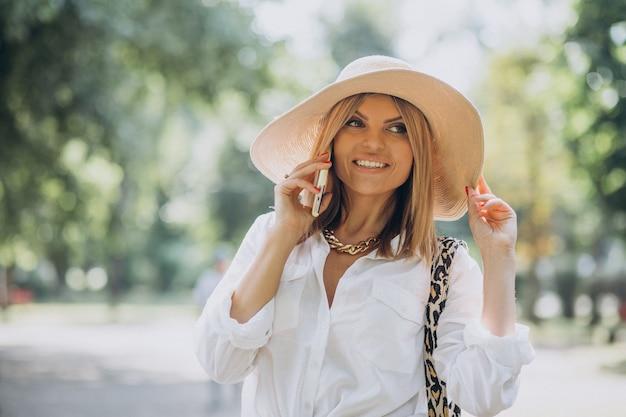 Frau, die im park geht und am telefon spricht