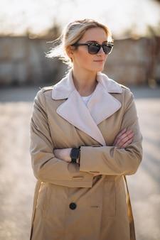 Frau, die im park im mantel steht
