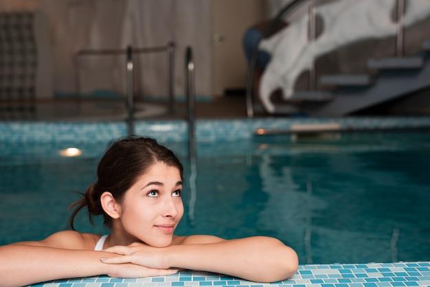 Frau, die im pool am badekurort aufwirft