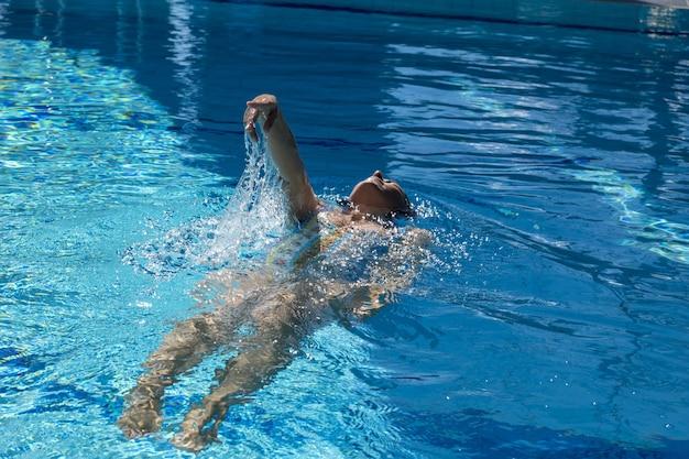 Frau, die im pool während des tages schwimmt