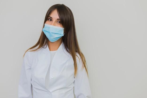 Frau, die im raum der chirurgischen maske und der kopie aufwirft