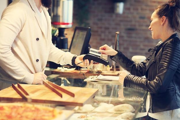 Frau, die im restaurant mit kreditkarte bezahlt
