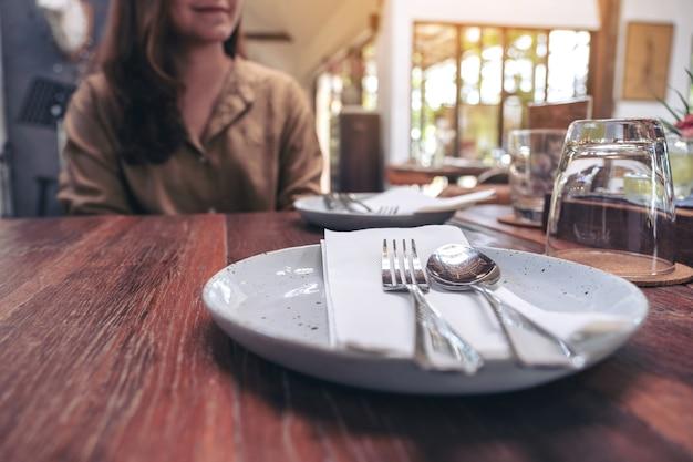 Frau, die im restaurant mit löffel und gabel in einem teller auf weinlese-holztisch sitzt