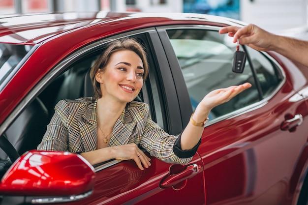 Frau, die im roten auto sitzt und schlüssel empfängt